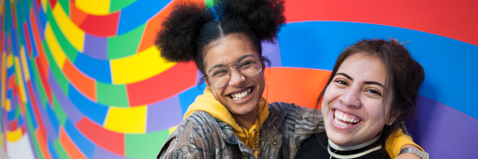 Photograph two smiling girls in front of LeWitt wall drawing